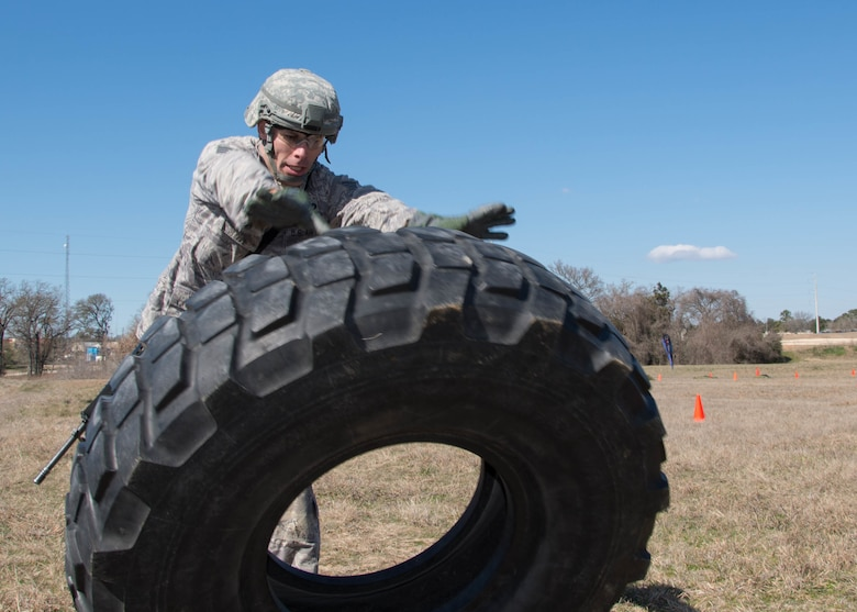 U.S. Air Force Tech. Sgt. Steven Hein, a competitor from the 136th Security Forces Squadron, conducts a tire flip as part of the mystery event portion of the Best Warrior Competition at Camp Swift, Texas, Feb. 6, 2016. The BWC test the aptitude of elite Texas Air and Army National Guardsmen in events relevant to today's operating environment. (Texas Air National Guard photo by Tech. Sgt. Vanessa Reed/ Released)