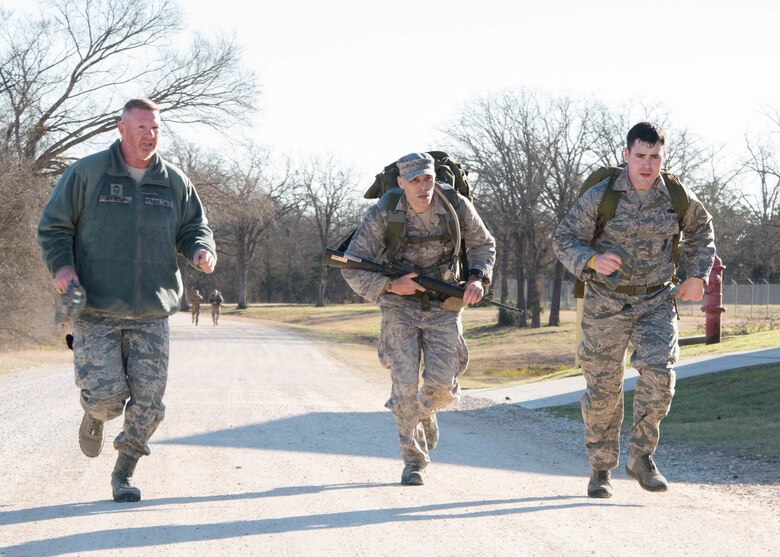 U.S. Air Force Staff Sgt. Steven Hein, an Air National Guard competitor, along with U.S. Air Force Chief Master Sgt. Del Atkinson and Tech. Sgt. Timothy Rooney, all from the 136th Security Forces Squadron, race to the end of an eight-mile ruck march during the Best Warrior Competition at Camp Swift, Texas, Feb. 6, 2015. The BWC test the aptitude of elite Texas Air and Army National Guardsmen in events relevant to today's operating environment. (Texas Air National Guard photo by Tech. Sgt. Vanessa Reed/ Released)