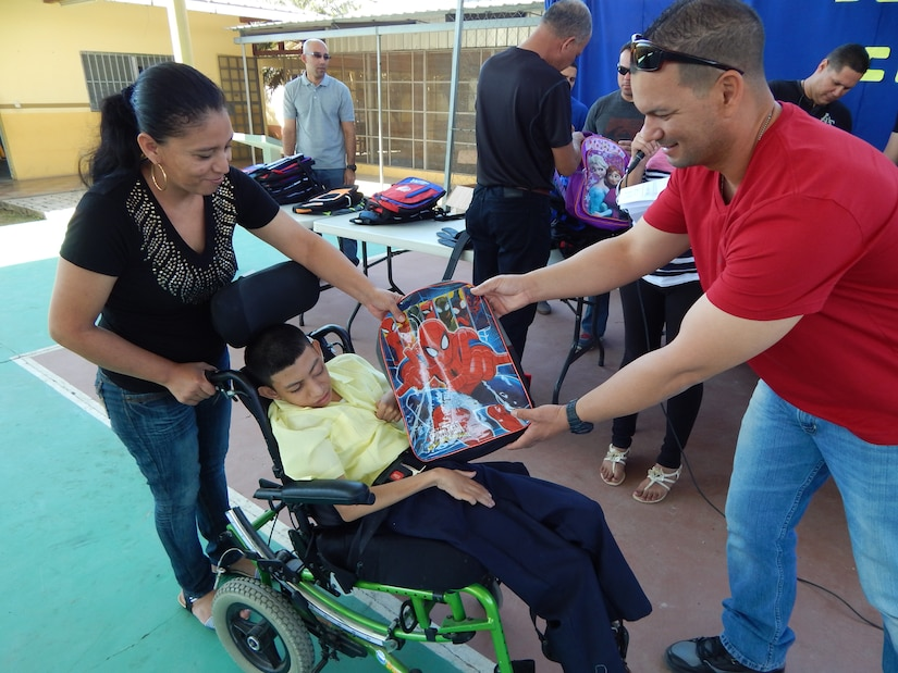 Comayagua, Honduras – U.S. Army Sgt. Miguel Robles, gives school materials to one of the children at CasAyuda, Comayagua, Honduras, Feb 02, 2016, during an activity sponsored by Joint Task Force-Bravo Joint Security Forces volunteers. Service members from JTF-Bravo volunteer their time to perform monthly visits to local orphanages to spend time with the children and give back to the community. (U.S. Army photo by SPC. Audie Colón)