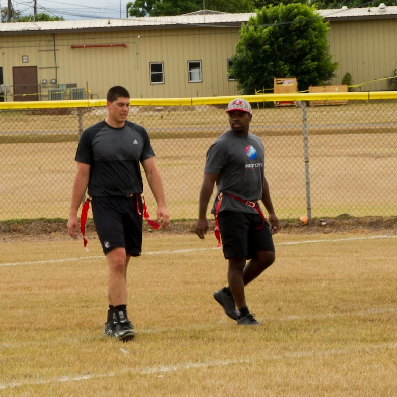 From left, U.S. Air Force 1st Lt. Benjamin Kopacka, 612th Air Base Squadron chief of engineering and Keith Tandy, Tampa Bay Buccaneers talk while playing in a flag football game Feb. 6, 2016 at Soto Cano Air Base, Honduras, during an NFL player and cheerleader visit with the Armed Forces Entertainment organization for Super Bowl 50. (U.S. Air Force photo by Capt. Christopher Mesnard/Released)