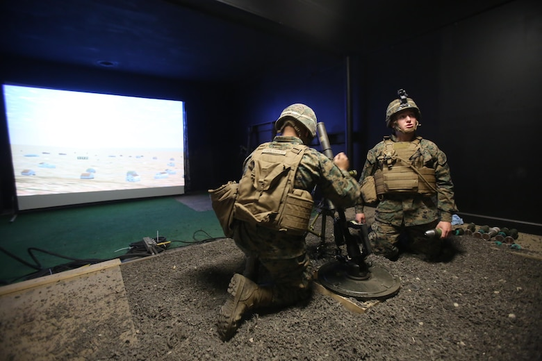 Two Marines conduct simulated mortar fires while training with the Division Combat Skills Center in the Indoor Simulated Marksmanship Trainer at Camp Lejeune, N.C., Jan. 27, 2016. This simulated motorman's pit provides a safer and more accurate way of honing their skills before firing live rounds. (U.S. Marine Corps photo by Cpl. Chelsea Toombs/Released)