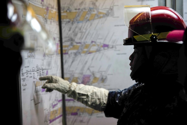 U.S. Navy Petty Officer 2nd Class Robert Castillo checks a damage control board during a fire drill on the USS Green Bay near Sasebo, Japan, Feb. 11, 2016. The Bay is attached to the Bonhomme Richard Amphibious Ready Group. Navy photo by Petty Officer 2nd Class Chris Williamson