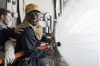 U.S. Navy Ensign Ty Downing demonstrates proper fire hose techniques during a general quarters drill in the hangar bay of the aircraft carrier USS Dwight D. Eisenhower, Feb. 9, 2016. Downing is the fire marshal on the Eisenhower, currently underway for the upcoming Board of Inspection and Survey. Navy photo by Petty Officer 3rd Class J. Alexander Delgado