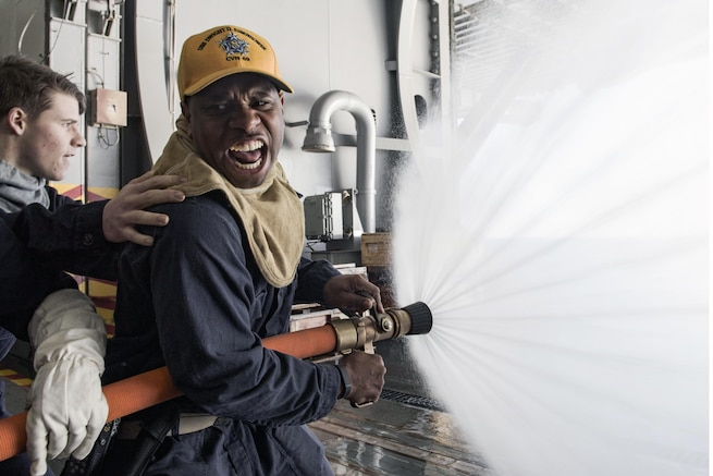 U.S. Navy Ensign Ty Downing demonstrates proper fire hose techniques during a general quarters drill in the hangar bay of the aircraft carrier USS Dwight D. Eisenhower, Feb. 9, 2016. Downing is the fire marshal on the Eisenhower. Navy photo by Petty Officer 3rd Class J. Alexander Delgado
