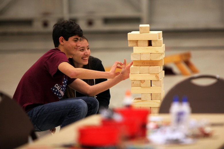 Caleb Passmore and Jasmin Tenorio play Jenga while attending the 7th annual Winter Wonderland at Marine Corps Air Station Cherry Point, N.C., Dec. 11, 2015. More than 700 Marines, Sailors and family members participate in the event. Winter Wonderland was hosted by Marine Aircraft Group 14 to foster camaraderie and increase esprit de corps within MAG-14 subordinate commands.