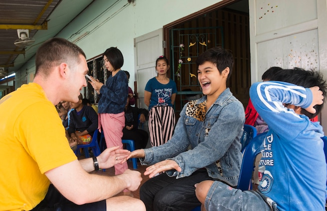 160207-N-RM689-536 SATTAHIP, Thailand (Feb. 7, 2016) - Lt. Shawn Callihan, assigned to amphibious dock landing ship USS Ashland (LSD 48), plays a hand game with children who attend Baan Kru Boonchoo for Special Children during a volunteering event. Ashland is assigned to the Bonhomme Richard Ready Group, and is participating in exercise Cobra Gold 16, a Thai- U.S. co-sponsored multinational joint exercise designed to advance regional security by exercising a robust multinational force from nations sharing common goals and security commitments in the Indo-Asia-Pacific region.
