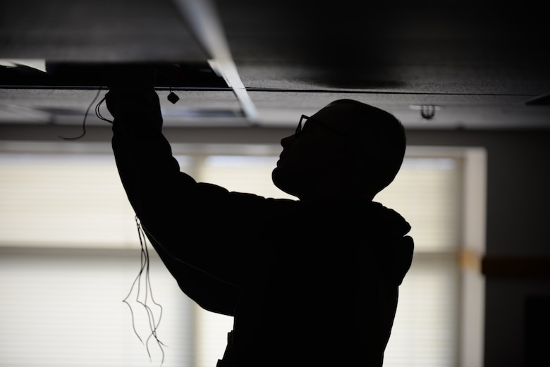 Senior Airman Daniel Hatfield, 28th Civil Engineer Squadron electrical systems technician, changes a phosphorous light fixture at Ellsworth Air Force Base, S.D., Jan. 26, 2016. Phosphorous bulbs are ignited by a ballast, which causes a small spark to light the phosphor in the bulbs to turn on the lights. (U.S. Air Force photo by Airman Sadie Colbert/Released)