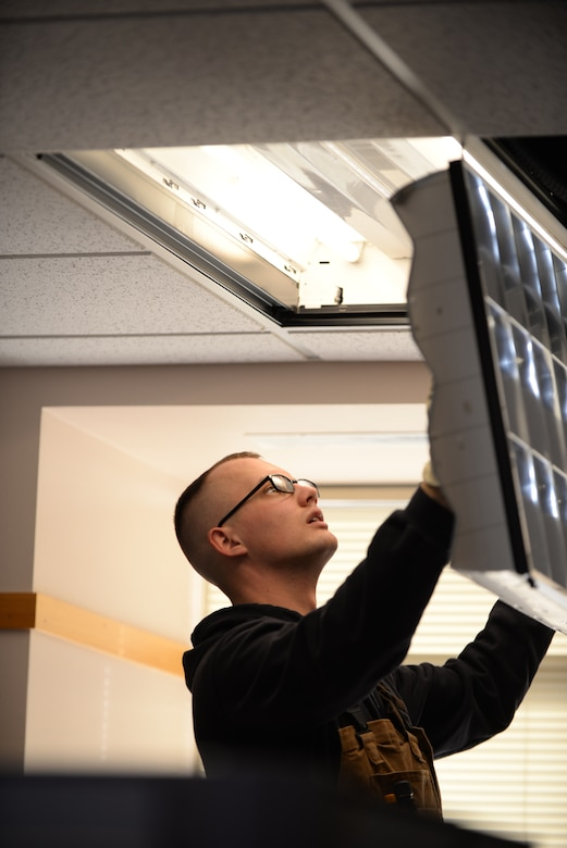 Senior Airman Daniel Hatfield, 28th Civil Engineer Squadron electrical systems technician, closes a diffuser to a light fixture at Ellsworth Air Force Base, S.D., Jan. 26, 2016. Diffusers are used to separate and lessen the harshness of light emitted by the bulb. (U.S. Air Force photo by Airman Sadie Colbert/Released)