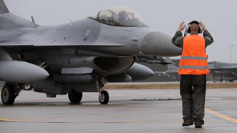 U.S. Air Force Senior Airman Andrew Burke, 31st Aircraft Maintenance Squadron dedicated crew chief, directs an F-16 Fighting Falcon for end-of-runway inspections before takeoff, Feb. 8, 2016, at Aviano Air Base, Italy. Team Aviano members must meet quarterly aircraft flying hours and adhere to the DUI Battle Plan to receive a wing goal day. (U.S. Air Force photo by Airman 1st Class Cary Smith/Released)