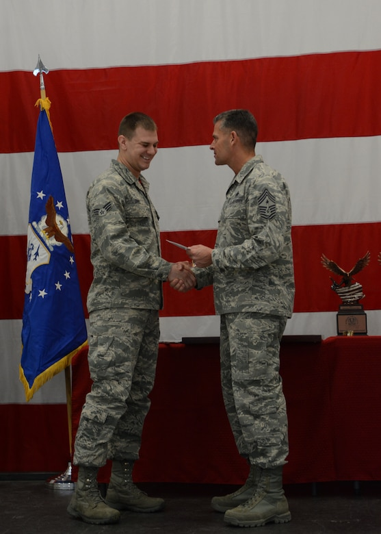 Senior Airman Troy Gibbs, 115th Fighter Wing operations group, accepts his Airman of the Year award from Chief Master Sgt. Thomas Safer, 115 FW command chief, during the first annual awards ceremony in Hangar 406 on Feb. 7, 2016. Several Airmen were recognized for their achievements during the ceremony. (U.S. Air National Guard photo by Staff Sgt. Andrea F. Rhode)