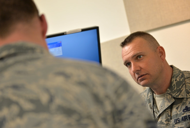 Chief Master Sgt. Michael Ditore, 432nd Wing/432nd Air Expeditionary Wing command chief, right, listens to Senior Airman Robert, 432nd Aircraft Communications Maintenance Squadron ground control station communications mechanic, as he explains how to conduct preventive maintenance inspections Feb. 11, 2016, at Creech Air Force Base, Nevada. Ditore's day consisted of wiping monitors and servicing parts of the GCS. (U.S. Air Force photo by Senior Airman Christian Clausen/Released)