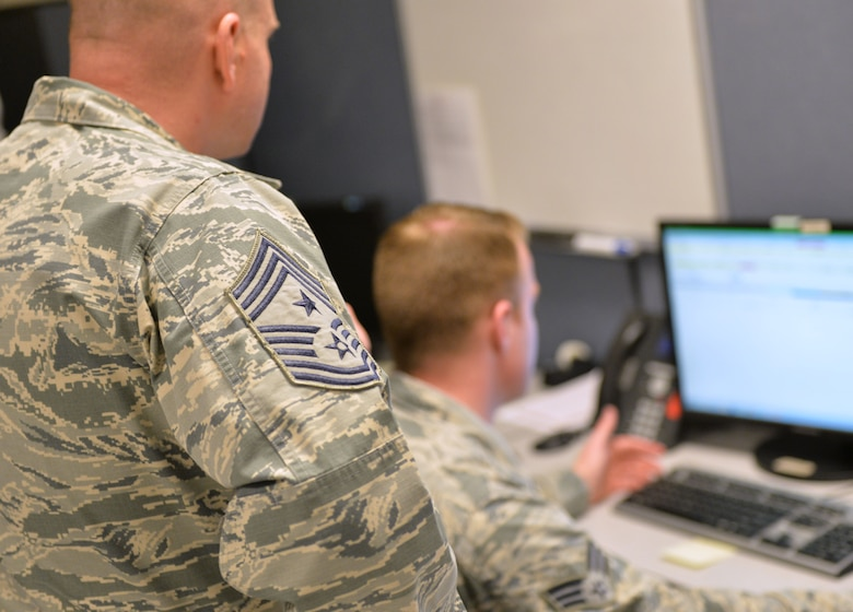 Chief Master Sgt. Michael Ditore, 432nd Wing/432nd Air Expeditionary Wing command chief, left, listens as Senior Airman Robert, 432nd Aircraft Communications Maintenance Squadron ground control station communications mechanic, explains how to fill out post-inspection paperwork Feb. 11, 2016, at Creech Air Force Base, Nevada. As a part of the communications squadron, Cameron is responsible for performing inspections on the ground control station. (U.S. Air Force photo by Senior Airman Christian Clausen/Released)