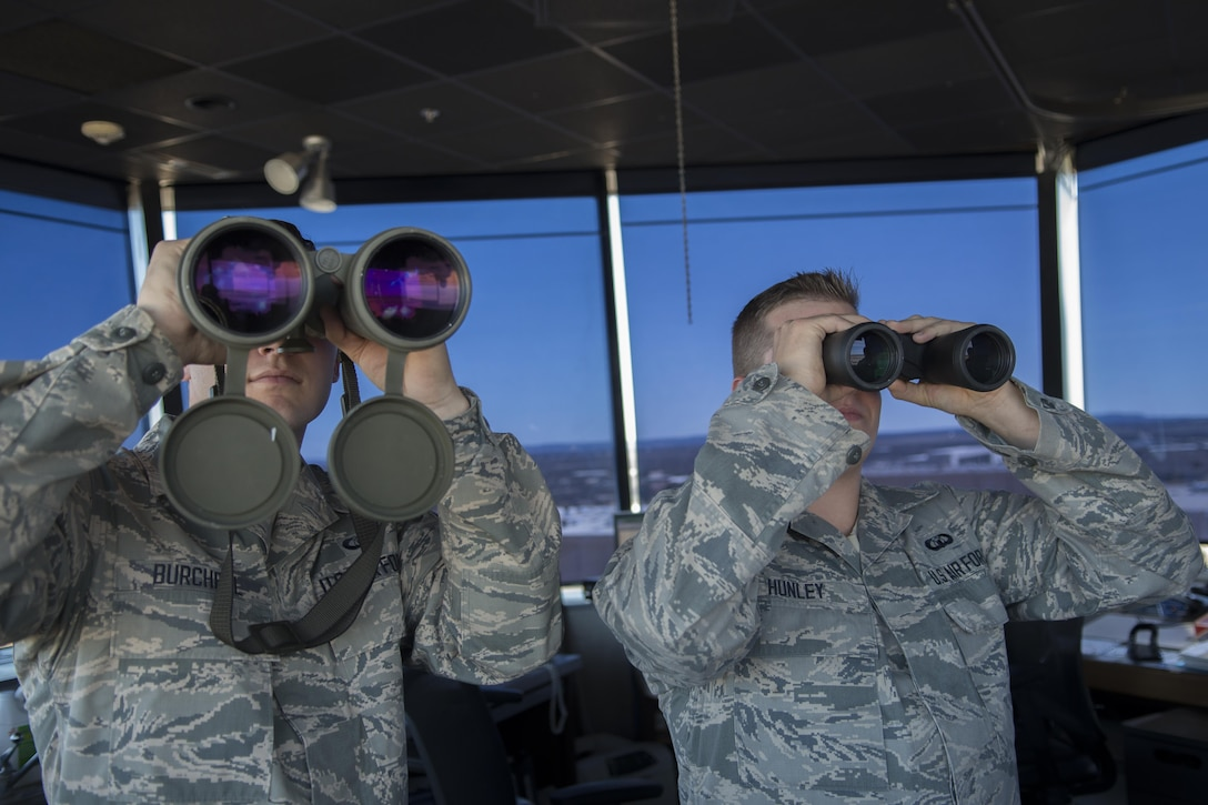 Airman 1st Class Brandon Burchell and Senior Airman Jakob Hunley, both 7th Operations Support Squadron air traffic controllers, scan the airfield using binoculars Jan. 25, 2016, at Dyess Air Force Base, Texas. Air traffic controllers scan the flightline to check for wildlife, watch for potential vehicular traffic interfering with air operations and to ensure the aircrafts' landing gear are down as they land. (U.S. Air Force photo/Airman 1st Class Austin Mayfield)