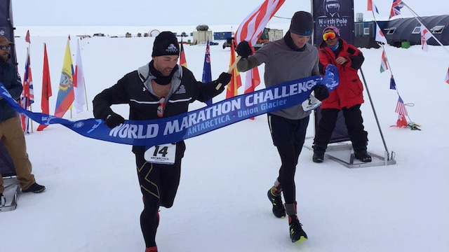 Captains Calum Ramm, left, and Daniel Cartica, right, cross a finish line during the World Marathon Challenge Jan. 23 at Union Glacier, Antarctica. The World Marathon Challenge is a seven-day event that encompasses seven marathons run on every continent. Cartica won the event with a cumulative time of 24 hours, 46 minutes and 56 seconds.