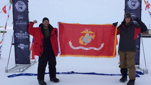 Captains Calum Ramm, left, and Daniel Cartica, right, hold the Marine Corps battle colors at the finish line during the World Marathon Challenge Jan. 23 at Union Glacier, Antarctica. The World Marathon Challenge is a seven-day event that encompasses seven marathons run on every continent. Cartica won the event with a cumulative time of 24 hours, 46 minutes and 56 seconds.