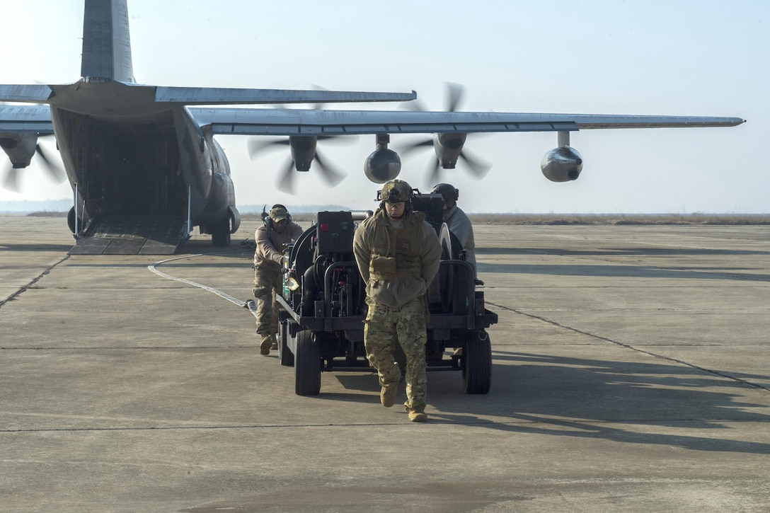 Members of the 100th Logistics Readiness Squadron move a forward area manifold cart out of the back of an MC-130J Commando II, assigned to the 67th Special Operations Squadron, during forward area refueling point training at Plovdiv, Bulgaria, Feb. 9, 2016. The FAM cart weighs approximately 3,500 pounds and is mainly extracted from the aircraft. (U.S. Air Force photo/Airman 1st Class Luke Kitterman)