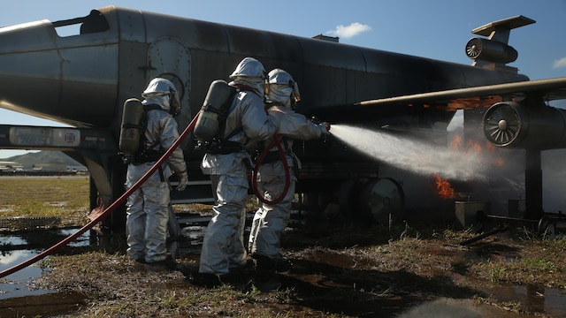 Marines with Air Rescue Fire Fighting train using fire suppression methods during burn training aboard Kaneohe Bay Marine Corps Air Station on Feb. 10, 2016. The mission of ARFF is to protect property and save lives, which means the Marines need to be suited up and moving out within seconds of a call. ARFF rescue men work together to prevent aircraft fires, house fires and any other emergency on the airfield and on base.