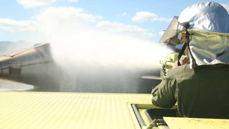 Pfc. Randy Gutierrez, an Air Rescue Fire Fighting turret operator with Kaneohe Bay Marine Corps Air Station, fires a water canon to cool down a simulated burning aircraft on Feb. 9, 2016. The mission of ARFF is to protect property and save lives, which means the Marines need to be suited up and moving out within seconds of a call. ARFF rescue men work together to prevent aircraft fires, house fires, and any other emergency on the airfield and on base.