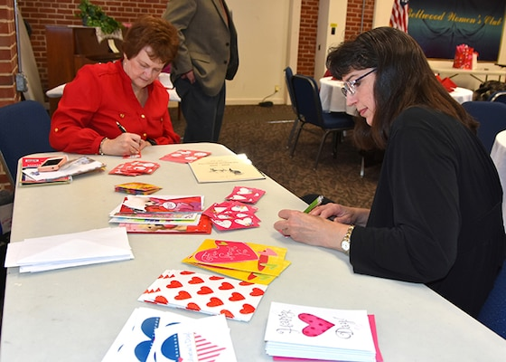 "Barbara Day (right), honorary president of the Bellwood Women's Club, and Sandy Wilkinson, co-chair of the club's Arrangements Committee, sign valentines for veterans during their monthly meeting Feb. 10, 2016 on Defense Supply Center Richmond, Virginia.  The cards are in support of the Department of Veterans Affairs' national ""Salute to Veteran Patients"" week."