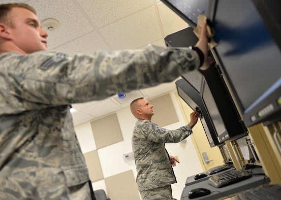 Chief Master Sgt. Michael Ditore, the 432nd Wing/432nd Air Expeditionary Wing command chief, right, cleans monitors with Senior Airman Robert, a 432nd Aircraft Communications Maintenance Squadron ground control station communications mechanic, Feb. 11, 2016, at Creech Air Force Base, Nev. They were wiping the screens as part of a preventative maintenance inspection. (U.S. Air Force photo/Senior Airman Christian Clausen)