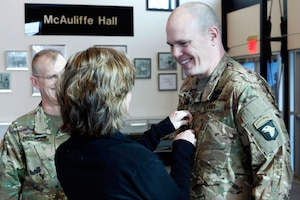 Lt. Col. Cory Mulhern, a liaison officer for the 101st Airborne Division (Air Assault), smiles at his daughter, Sierra, as she pins on his rank during his promotion ceremony in the division headquarters, Fort Campbell, Kentucky, Feb. 11, 2016. Mulhern, a guardsman with the Wisconsin National Guard, is part of the 101st's multi-component unit, a pilot program where Guard and active duty Soldiers train and deploy together.
