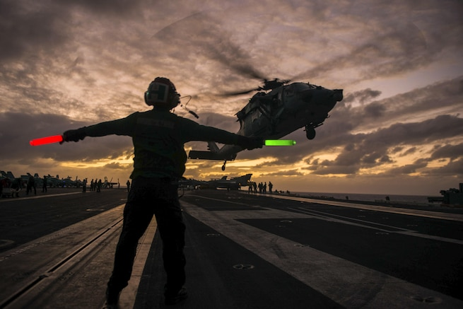 Navy Airman Tuan Hoang signals to an MH-60S Seahawk as it takes off from the flight deck of the USS John C. Stennis in the Pacific Ocean, Feb. 11, 2016. The Seahawk is assigned to Helicopter Sea Combat Squadron 14. Navy photo by Seaman Cole C. Pielop