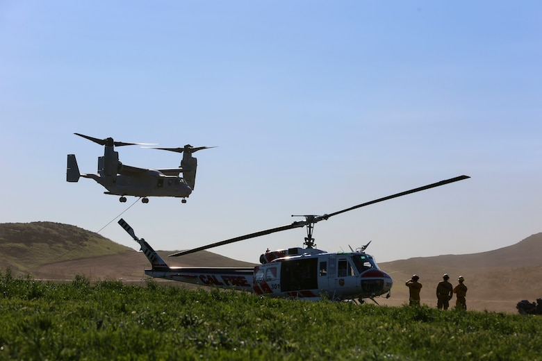 An MV-22B Osprey with Marine Medium Tiltrotor Squadron (VMM) 165 takes off to load the bucket while performing firefighting training while the California Department of Forestry and Fire Protection firefighters watch from below aboard Hemet-Ryan Air Attack Base, Calif., Feb. 11. The Marines with VMM-165 flew out to Diamond Valley Lake on Hemet-Ryan Air Attack Base to perform bucket dips in an effort to prove the aircraft was capable of such training while supporting Cal Fire.