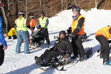Marcus Brumbaugh, an electrical mechanic from the Nashville District helps skiers during the 35th Disabled Sports USA Adaptive Learn to Ski event clinic held Jan. 19, 2016 at the Beech Mountain Resort in Beech Mountain, N.C. Since 1981, the adaptive sports program has been offering risk reduced and highly supportive ski lessons for adults and children with a wide array of disabilities.