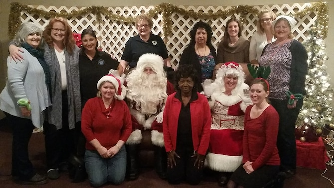 Members of the Enlisted Spouses Club Winter Wonderland Committee stand around Santa Clause at the 21st Annual Winter Wonderland at the Bellevue Social Center, Bellevue, Neb., Dec. 12, 2015. The event provides gifts and activities for the children of active duty or retired service members. (Courtesy photo)