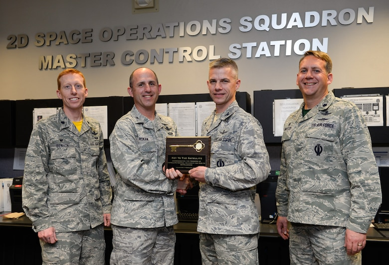 Lt. Col. Todd Benson, 2nd Space Operations Squadron commander, Col. Michael Rokaw, Space and Missile Systems Center's  GPS Space Segment Division chief, Col. Stephen Slade, Individual Mobilization Augmentee to the 50th Space Wing commander, and Lt. Col. Samuel Baxter, 19th Space Operations Squadron commander, pose with a symbolic key after the 50th Space Wing assumed satellite control authority of SVN-70, a GPS IIF-12 satellite, from 14th Air Force (Air Forces Strategic) in a short ceremony Feb. 12 at Schriever Air Force Base, Colo. This satellite is the last in a demanding schedule of IIF satellite launches; the units have teamed together to support six launches in just 18 months.  (U.S. Air Force photo/Christopher DeWitt)