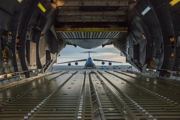 A C-5 Galaxy is framed by the opened aft cargo door of another C-5 Super Galaxy Feb.  4 at Travis Air Force Base, California. Travis recently completed Crisis Look 16-0, an operational readiness inspection designed to evaluate how quickly personnel base wide can mobilize and move people, heavy equipment and whatever else is needed to anywhere in the world at a moments'  notice when called upon in an emergency situation. (U.S. Air Force photo by Heide Couch)