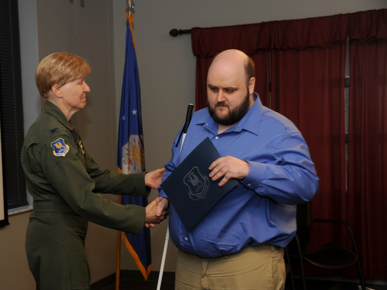 Joseph Lininger, Civilian Acculturation and Leadership Training student, receives his graduation certificate from Col. Patricia Hoffman, vice commander of the Jeanne M. Holm Center for Officer Accessions and Citizen Development, during the CALT graduation of class 16-03 Feb. 5, 2016, at Maxwell Air Force Base, Alabama. Lininger was the first blind student to attend and graduate from the CALT course. (U.S. Air Force photo by Airman 1st Class Alexa Culbert)