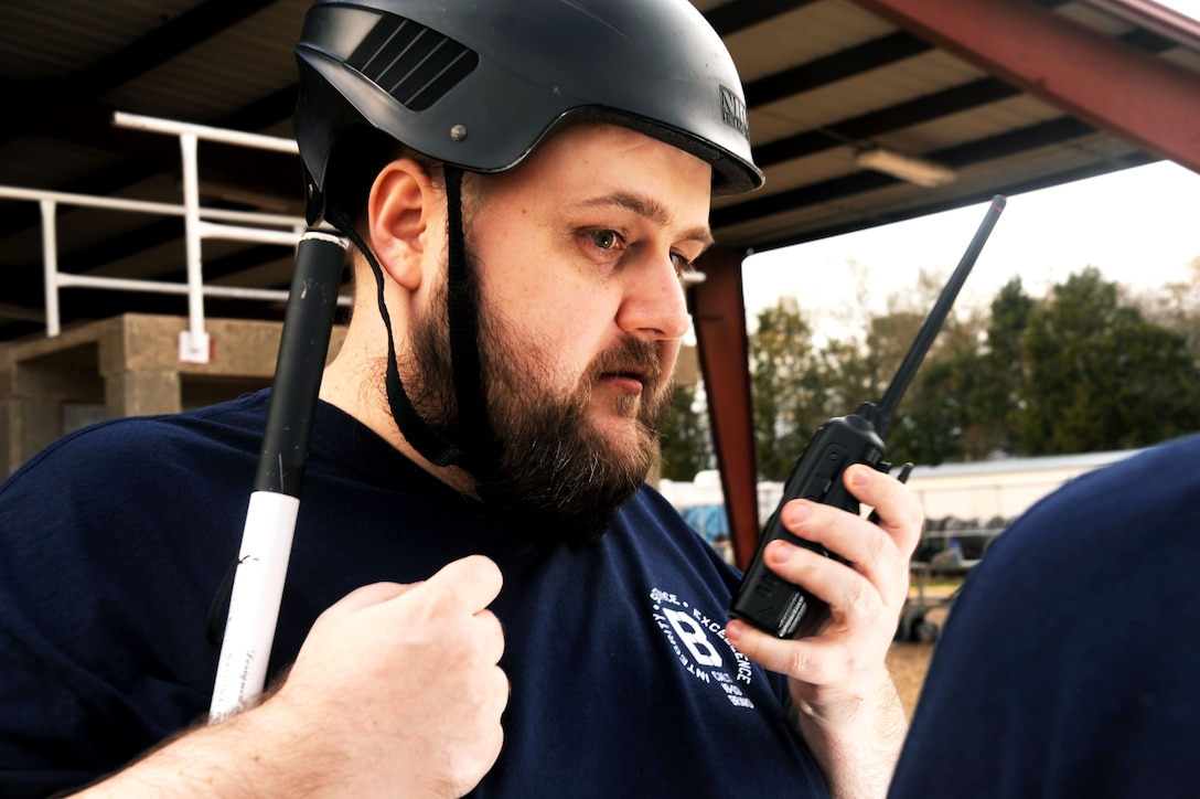 Joseph Lininger, Civilian Acculturation and Leadership Training student, guides his classmates using a radio as they maneuver through a Project X obstacle Feb. 2, 2016, at Maxwell Air Force Base, Alabama. Because he is blind, he was not able to physically participate in the obstacles. However, Lininger guided his classmates by playing the part of a commanding officer who is not physically with his unit. (U.S. Air Force photo by Airman 1st Class Alexa Culbert)