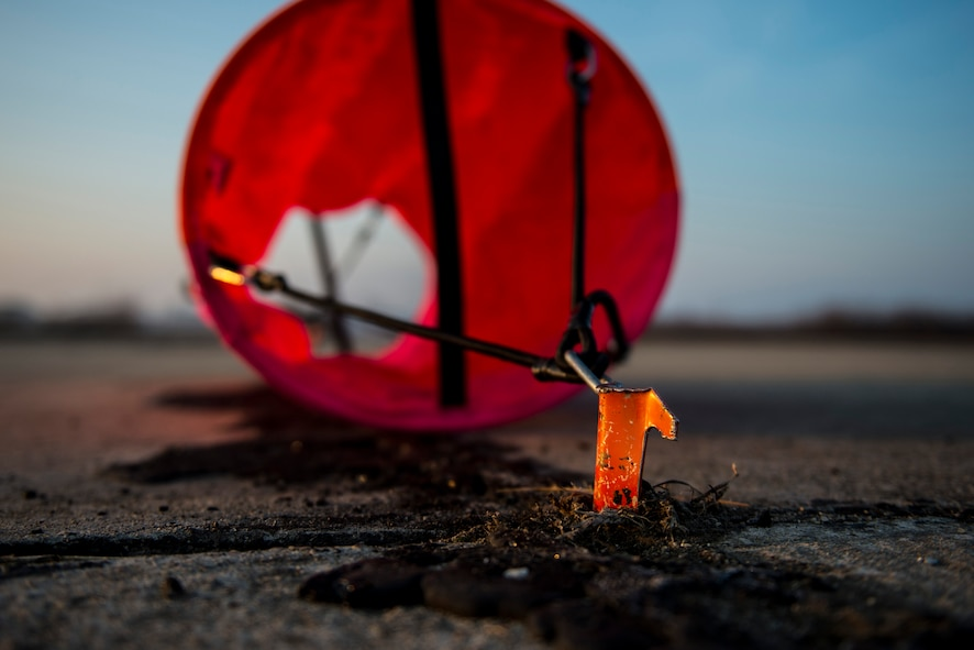 A distance marker is held in position on an unimproved surface during an austere landing exercise at Plovdiv, Bulgaria, Feb. 9, 2016. The colorful markers were put in place by 321st Special Tactics Squadron combat controllers and are used as a visual reference point to aid pilots when landing on unmarked surfaces. (U.S. Air Force photo by Airman 1st Class Luke Kitterman/Released)