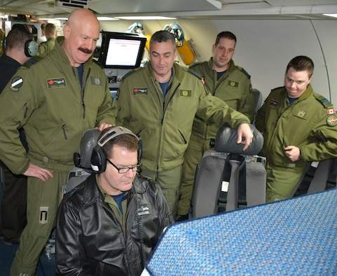 """Lt. Gen. Mike Hood, commander of the Royal Canadian Air Force, seated, listens to a recording of a recent mission performed by members of the 552nd Air Control Wing during a tour of an E-3 """"Sentry"""" Airborne Warning and Control System Block 40/45 aircraft on Feb. 3 at Tinker Air Force Base. Looking over the general's shoulder and taking part in the E-3 static display are, from left, Maj. Gordon Lemon, mission crew commander; Lt. Col. Donald Saunders, 552nd ACW Canadian Detachment commander; Capt. Andrew Baier, airborne surveillance officer; and Capt. Anthony Snow, senior director. General Hood, assigned to the National Defense Headquarters in Ottawa, visited with the Canadian Detachment that consists of 39 members of the Royal Canadian Air Force and three members of the Canadian Army. During his visit, the general also met with Col. David Gaedecke, 552nd ACW commander, and held a commander's call with members of the detachment. The partnership between the Canadian Detachment, which falls under the 552nd ACW, is now in its 36th year. The Detachment first began working with the 552nd ACW in 1979. (Air Force photo by Darren D. Heusel/Released)"""