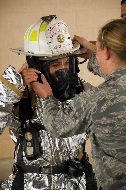 Senior Airman Adrianna Hopkins, 612th Air Base Squadron firefighter helps Cassia Gass, Indianapolis Colts cheerleader, don equipment the 612th uses to respond to and fight fires Feb. 7, 2016 at Soto Cano Air Base, Honduras. NFL cheerleaders and players took time to meet with members of the base as a part of a visit to the base hosted by the Armed Forces Entertainment for Super Bowl 50. (U.S. Air Force photo by Capt. Christopher Mesnard/Released)