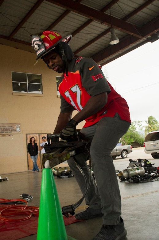 Keith Tandy, Tampa Bay Buccaneers safety attempts to pick up an egg to demonstrate the precision and dexterity of a devise emergency responders use to manipulate metal and other materials Feb. 7, 2016 at Soto Cano Air Base, Honduras. NFL cheerleaders and players took time to meet with members of the base as a part of a visit to the base hosted by the Armed Forces Entertainment for Super Bowl 50. (U.S. Air Force photo by Capt. Christopher Mesnard/Released)