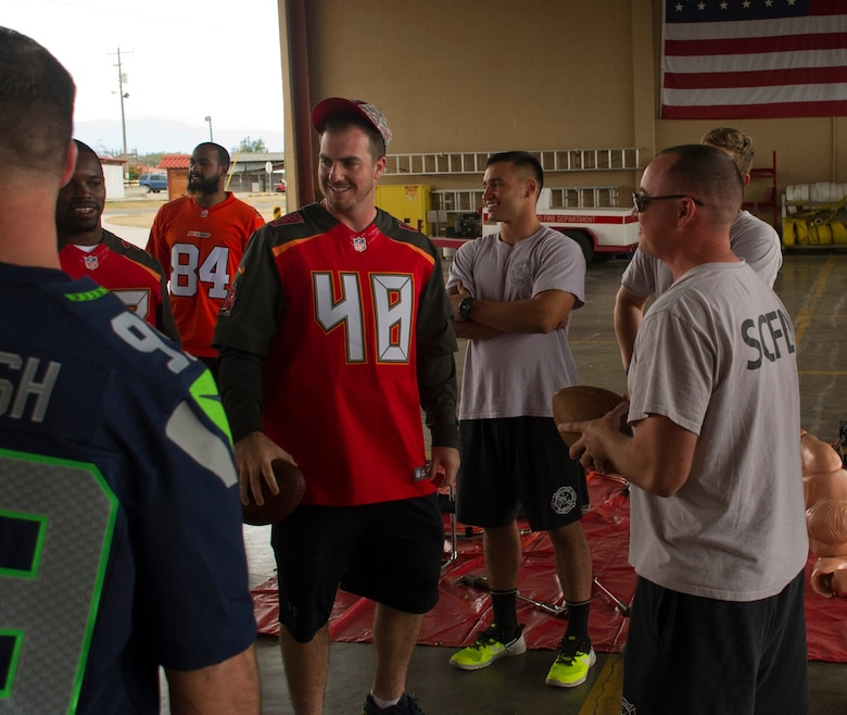 Firefighters with the 612th Air Base Squadron interact with NFL football players Feb. 7, 2016 at Soto Cano Air Base, Honduras as a part of a visit to the base hosted by the Armed Forces Entertainment for Super Bowl 50. (U.S. Air Force photo by Capt. Christopher Mesnard/Released)