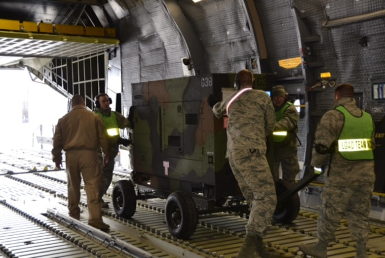 Airmen load cargo onto an aircraft in preparation for the 174th Attack Wing's deployment from Hancock Field Air National Guard Base in January, 2016. (Courtesy photo/Released)