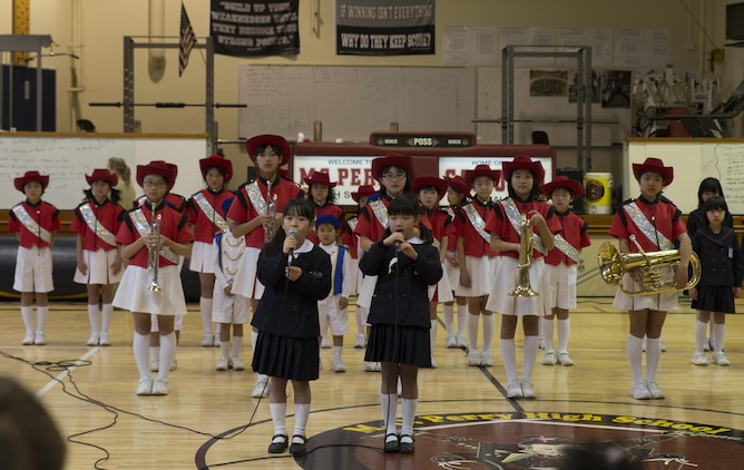 """Eight-year-old Chinatsu Moriwaki and Sae Matsumoto, students of Fukugawa Elementary School, sing the """"Star Spangled Banner"""" during a cultural exchange at Matthew C. Perry Elementary School Feb. 11, 2016. Fukugawa Elementary School is a member of the Shunan International Children's Club that visits M.C. Perry Elementary School annually. Approximately 90 children's club students, staff and government officials attended the cultural exchange."""