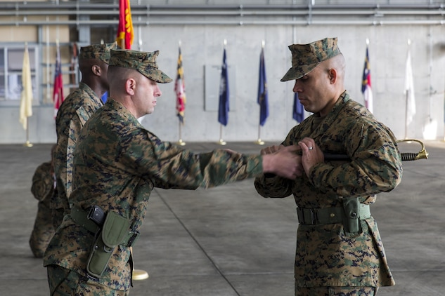 Lt. Col. Kolter Miller, left, Marine Aviation Logistics Squadron 12 commanding officer, passes the sword of office to Sgt. Maj. Edwin Mota, newly appointed MALS-12 sergeant major, during a relief and appointment ceremony at Marine Corps Air Station Iwakuni, Japan, Feb. 12, 2016. Sgt. Maj. Darnell Richardson, outbound MALS-12 sergeant major, relinquished his duties to Mota. The passing of the sword of office represents the transferring of duties and responsibilities from one sergeant major to another.