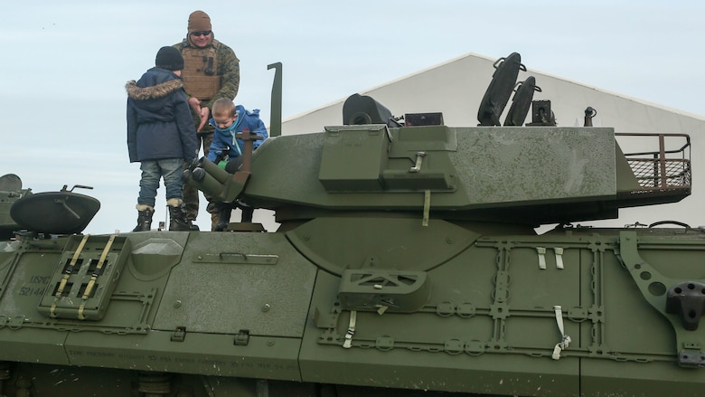 A Marine with 2nd Marine Expeditionary Brigade shows local children around a light armored vehicle at Hell Station in Hell, Norway, Feb. 12. Tons of combat vehicles and equipment were transported by rail to Rena, Norway, where the 2nd Marine Expeditionary Brigade's ground combat element will take part in live-fire exercise in the coming days. The rail operations moved vehicles and equipment prepositioned in caves here to the training area in preparation for Exercise Cold Response 16, comprised of 13 allied and partner nations, and over 16,000 troops, starting later this month.