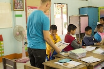 U.S. Marine Corps Lance Cpl. Otto Duerk an Aviation Operations Specialist with Marine Light Attack Helicopter Squadron 167 hands out coloring books at the Wat Samnak Ka Thon School, Rayong District, Thailand, during exercise Cobra Gold, Feb. 9, 2016. Cobra Gold, in its 35th iteration, includes a specific focus on humanitarian civic action, community engagement, and medical activities conducted during the exercise to support the needs and humanitarian interests of civilian populations around the region.