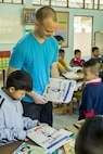 U.S. Marine Corps Lance Cpl. Otto Duerk an Aviation Operations Specialist with Marine Light Attack Helicopter Squadron 167, a native of Sarasota, Fla., hands out coloring books at the Wat Samnak Ka Thon School, Rayong District, Thailand, during exercise Cobra Gold, Feb. 9, 2016. Cobra Gold, in its 35th iteration, includes a specific focus on humanitarian civic action, community engagement, and medical activities conducted during the exercise to support the needs and humanitarian interests of civilian populations around the region.