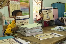 Children at the Wat Samnak Ka Thon School, Rayong District, Thailand, receive coloring books from U.S. Marines during exercise Cobra Gold, Feb. 9, 2016. Cobra Gold, in its 35th iteration, includes a specific focus on humanitarian civic action, community engagement, and medical activities conducted during the exercise to support the needs and humanitarian interests of civilian populations around the region.