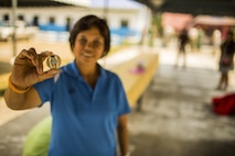 Upin Tain Chumpun, school director, holds a coin during the construction of a classroom at the Wat