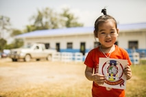 A child holds a sticker during the construction of a classroom at the Wat Ban Mak school, Saraburi, Thailand, during exercise Cobra Gold, Feb. 14, 2016. Cobra Gold, in its 35th iteration, focuses on humanitarian civic action, community engagement, and medical activities to support the needs and humanitarian interest of civilian populations around the region.