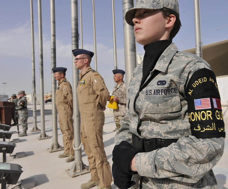 Senior Airman Nikole Warn, Al Udeid Air Base Honor Guard member, stands in position with German Air Force members during a flag raising ceremony at Al Udeid Air Base, Qatar, Feb. 8, 2016. The ceremony recognized the addition of Germany to the coalition supporting Operation Inherent Resolve. (U.S. Air Force photo by Master Sgt. Joshua Strang)