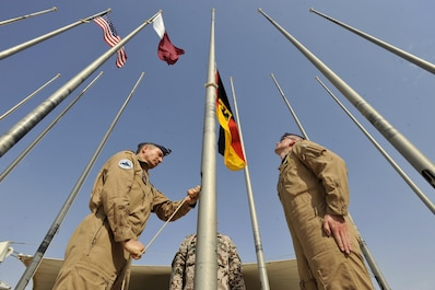 German Air Force members raise the German flag during a ceremony at Al Udeid Air Base, Qatar, Feb. 8, 2016. The ceremony recognized the addition Germany to the coalition supporting Operation Inherent Resolve. (U.S. Air Force photo by Master Sgt. Joshua Strang)