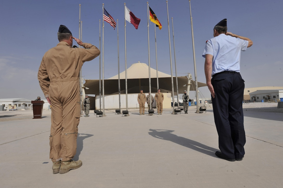 Lt. Gen. Joachim Wundrak (right), commander, German Air Operations Command and German Air Force Col. Gerhard Roubal, salute during a German flag raising ceremony at Al Udeid Air Base, Qatar, Feb. 8, 2016. The ceremony recognized the addition of Germany to the coalition supporting Operation Inherent Resolve. (U.S. Air Force photo by Master Sgt. Joshua Strang/Released)
